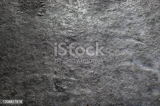 833130962 istock photo Icy road. Selective focus. Hazard concept ice-crusted ground. Black and white image. 1208617316