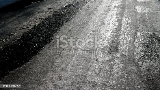 833130962 istock photo Icy road. Selective focus. Hazard concept ice-crusted ground. Black and white image. 1209985757