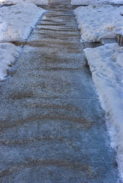Icy sidewalk and gravel stock photo
