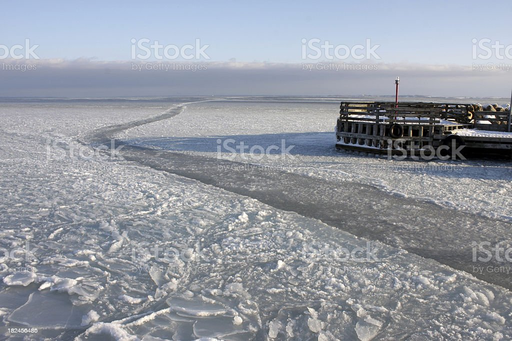 Icy winter path leading out of Danish harbor. royalty-free stock photo