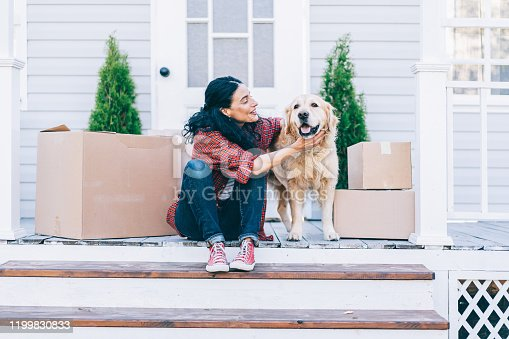 Мid adult woman moving to new house and sitting on the stairs and petting her golden retriever