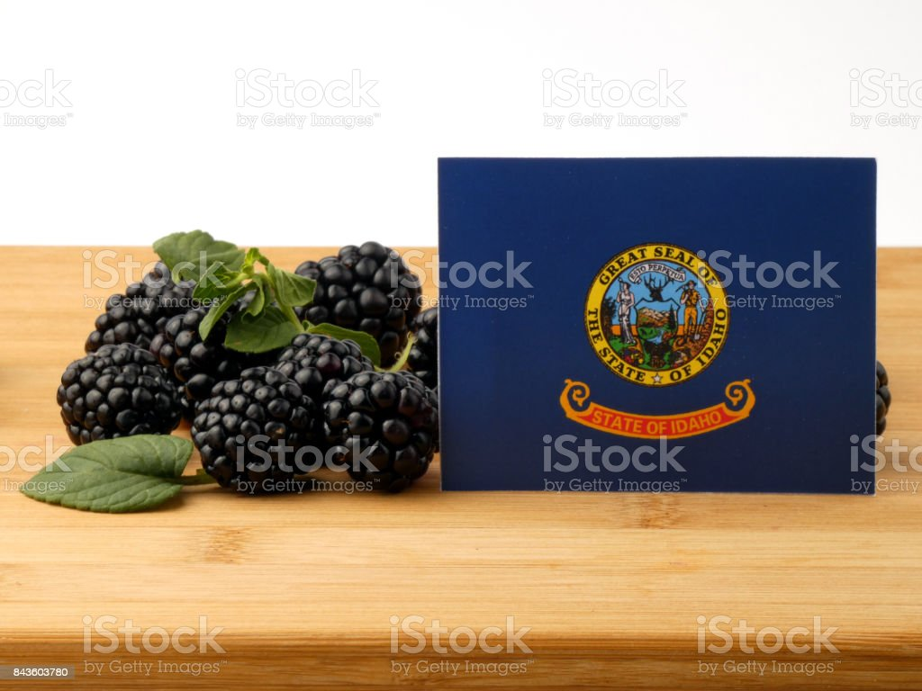 Idaho flag on a wooden panel with blackberries isolated on a white background stock photo
