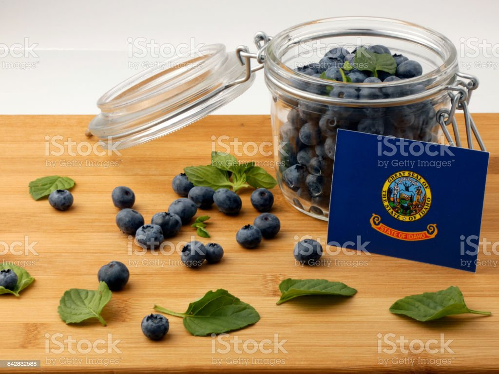 Idaho flag on a wooden plank with blueberries isolated on white stock photo