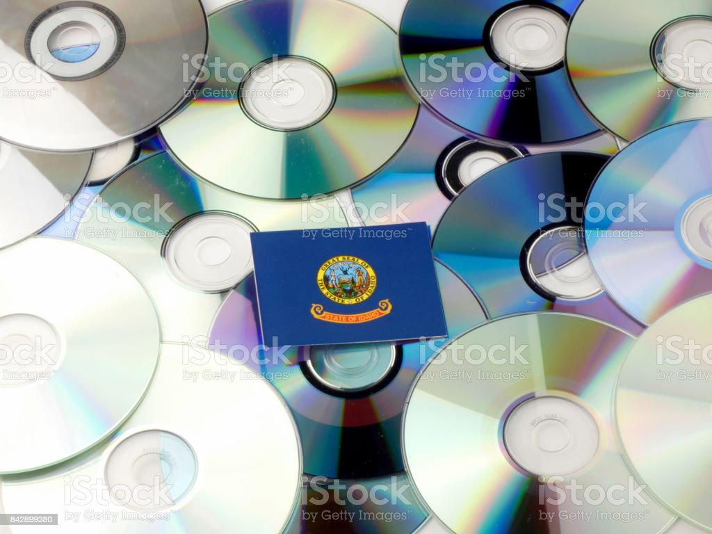 Idaho flag on top of CD and DVD pile isolated on white stock photo