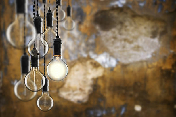 idea and leadership concept vintage  bulbs on wall background - business symbols stock photos and pictures