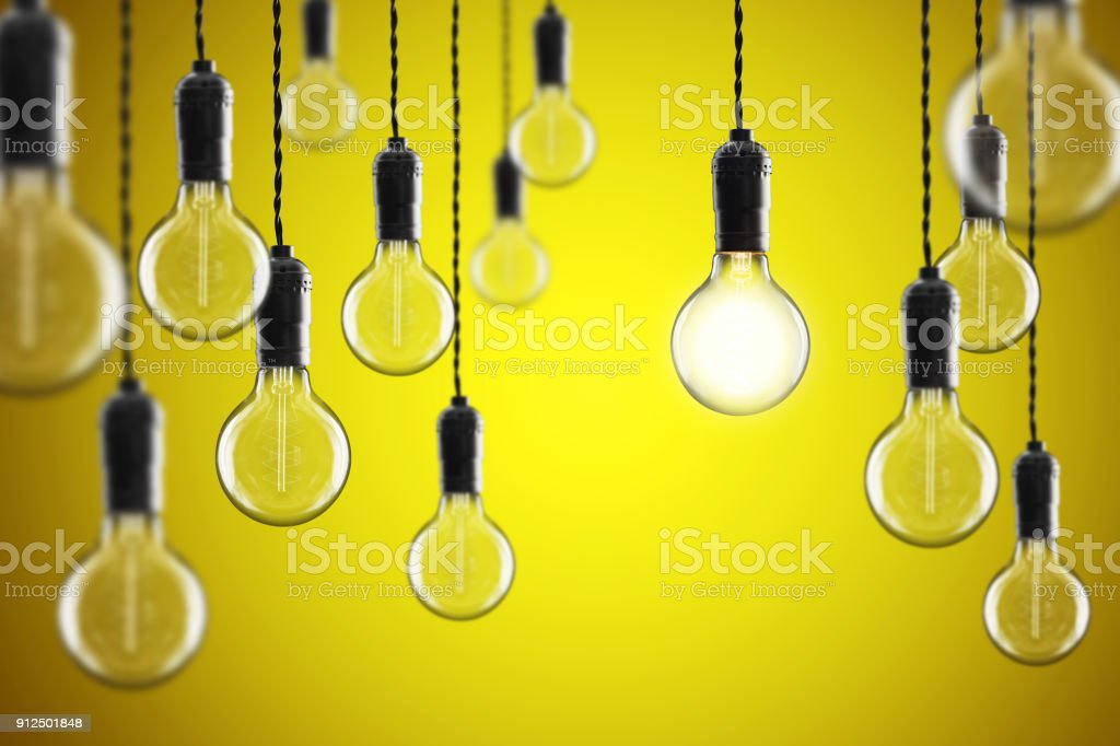Idea and leadership concept Vintage incandescent Edison bulbs on color background stock photo