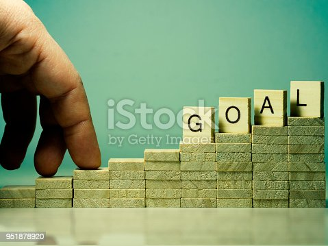 958939552istockphoto idea and purpose - oriented concept visual. Goal text and two fingers climbing up the stairs 951878920