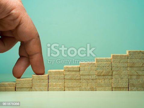 958939552istockphoto idea and purpose-oriented concept visual for business. fingers up the stairs 951875056