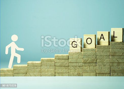 958939552istockphoto idea and purpose-oriented concept visual for business. the man up the stairs and the goal text 951875328