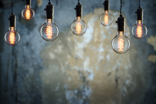 Idea and leadership concept Vintage  bulbs on wall background,  copy space for text