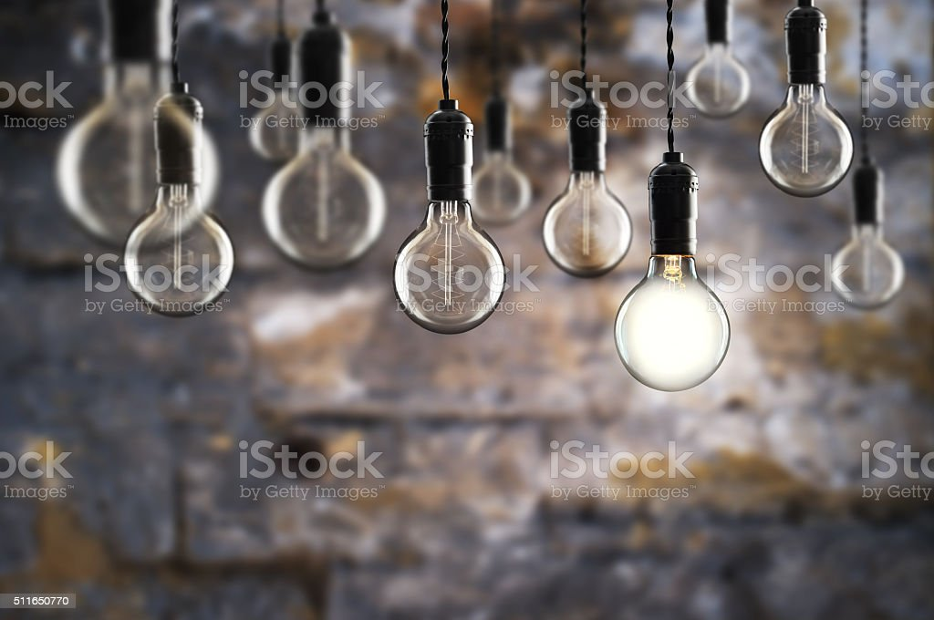 Idea and leadership concept Vintage bulbs on wall background, copy...