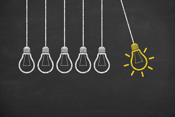 idea bulb concept drawing on blackboard - illustrations stock photos and pictures