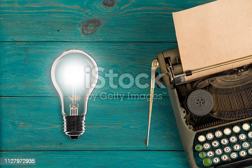 istock Idea concept- Vintage bulb and typewriter 1127972935