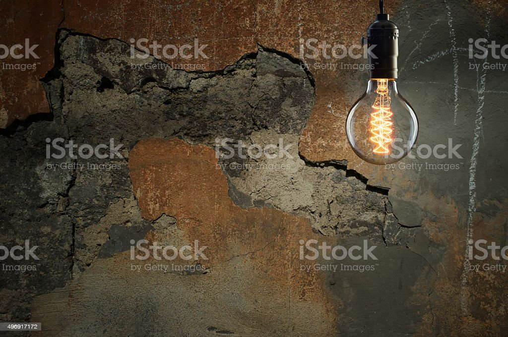 Idea concept - Vintage incandescent bulb on wall background stock photo