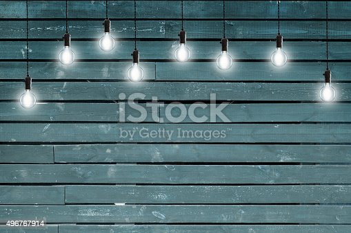 istock Idea concept - Vintage incandescent bulbs on blue wooden wall 496767914