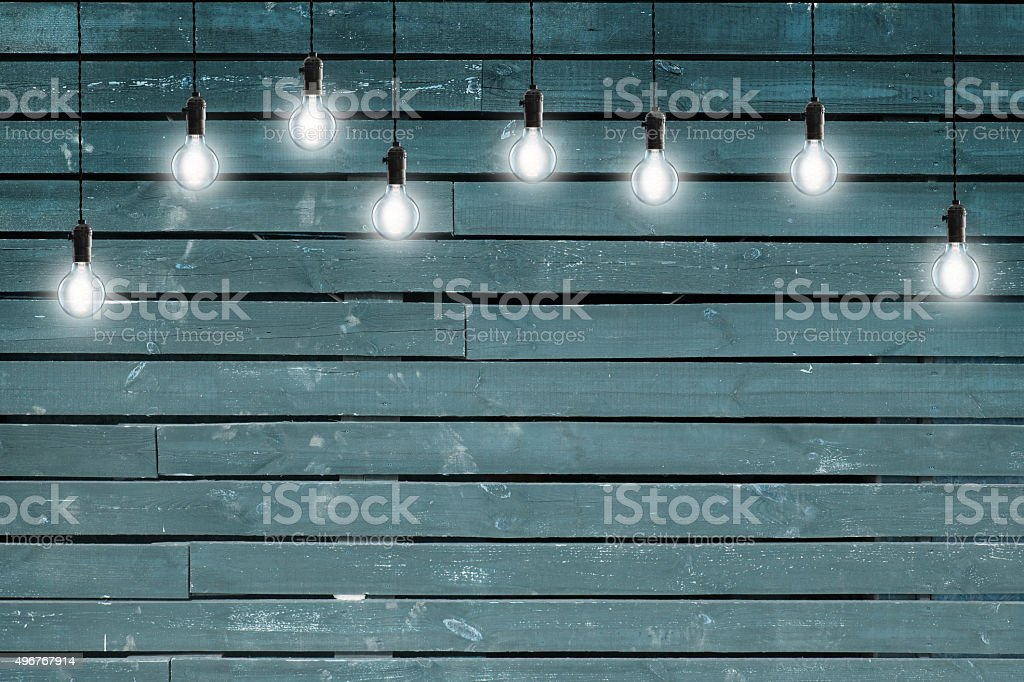 Idea concept - Vintage incandescent bulbs on blue wooden wall stock photo