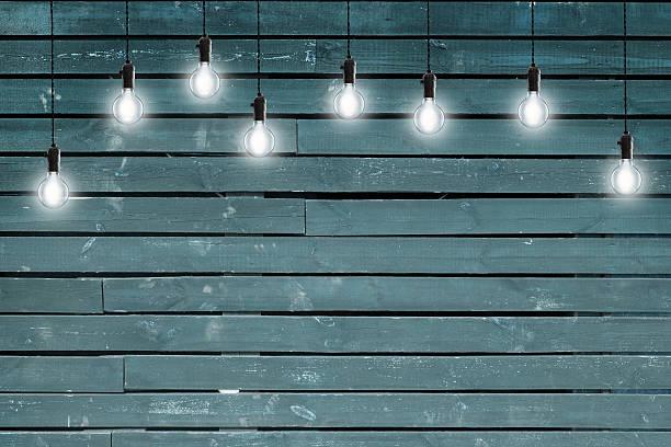 idee konzept-vintage funkelnden glühbirnen auf blau holz wand - terrassen deck design stock-fotos und bilder