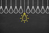 istock Idea concept with light bulbs on a blackboard background 935215014