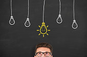 istock Idea concept with light bulbs on a chalkboard background 917522264