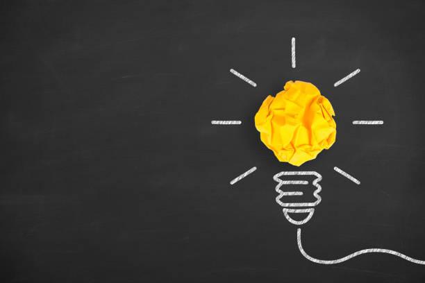 Ideenkonzepte Glühbirne zerknittert gelbes Papier auf Tafel Hintergrund – Foto
