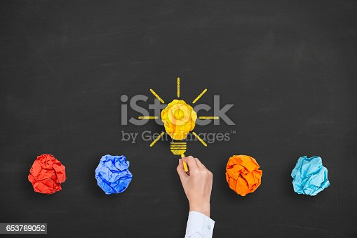 istock Idea Concepts Light Bulb Crumpled Yellow Paper on Chalkboard Background 653769052