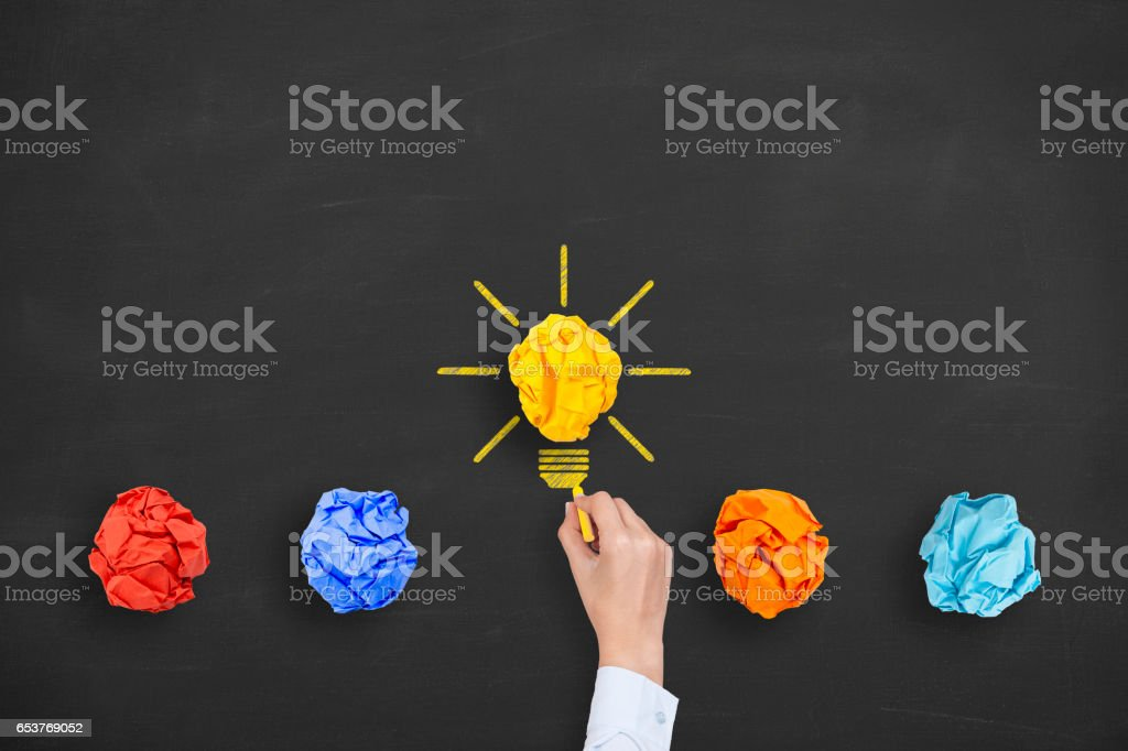 Idea Concepts Light Bulb Crumpled Yellow Paper on Chalkboard Background stock photo