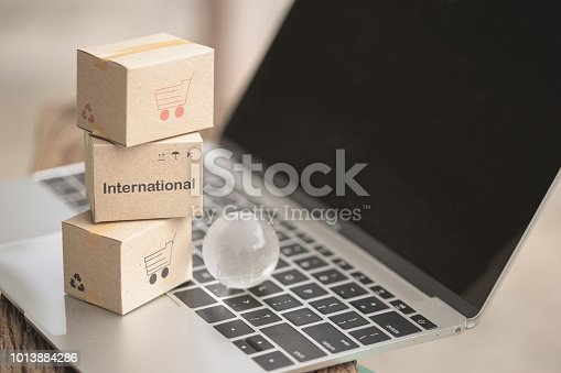 868776578istockphoto Idea International shipping and service / e-commerce concept. Stack boxes on tablet computer for Customer can buy from electronic internet and the messenger from delivery. 1013884286