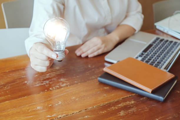 Idea of business person holding light bulb concept creativity with bulbs. stock photo