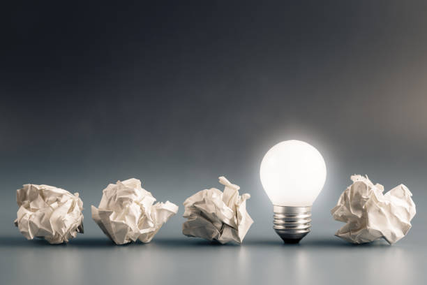 Idea Solution Small light bulb glowing in a row of crumpled paper balls, inspiration, problem and solution concept mistake stock pictures, royalty-free photos & images