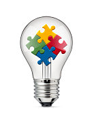 Idea and Solution. Light bulb with colored jigsaw puzzle on white background.