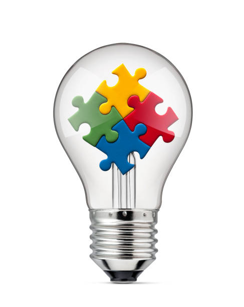 Idea Solutions. Light bulb with colored jigsaw puzzle. stock photo