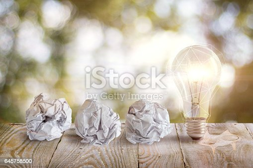 istock Idea with a crumpled office paper and light bulb . 645758500