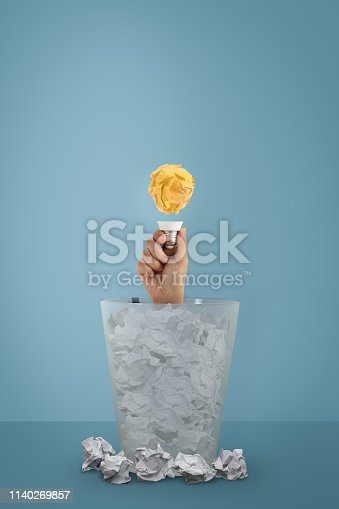 1162297213 istock photo Idea with paper ball and lightbulb, The woman's hand appeared from the trash. 1140269857