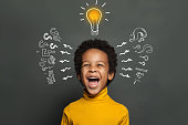 istock Ideas and brainstorm concept. Happy child school student with lightbulb and chalk question marks 1221651901