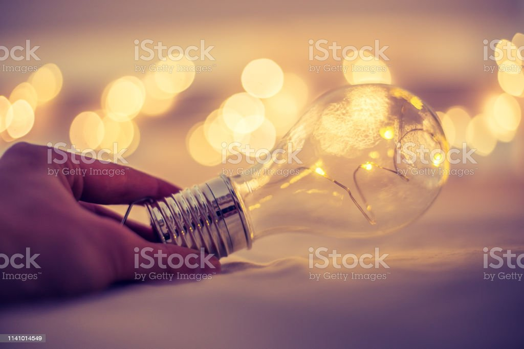 LED light bulb is lying in the bed, hands touching. Symbol for ideas...