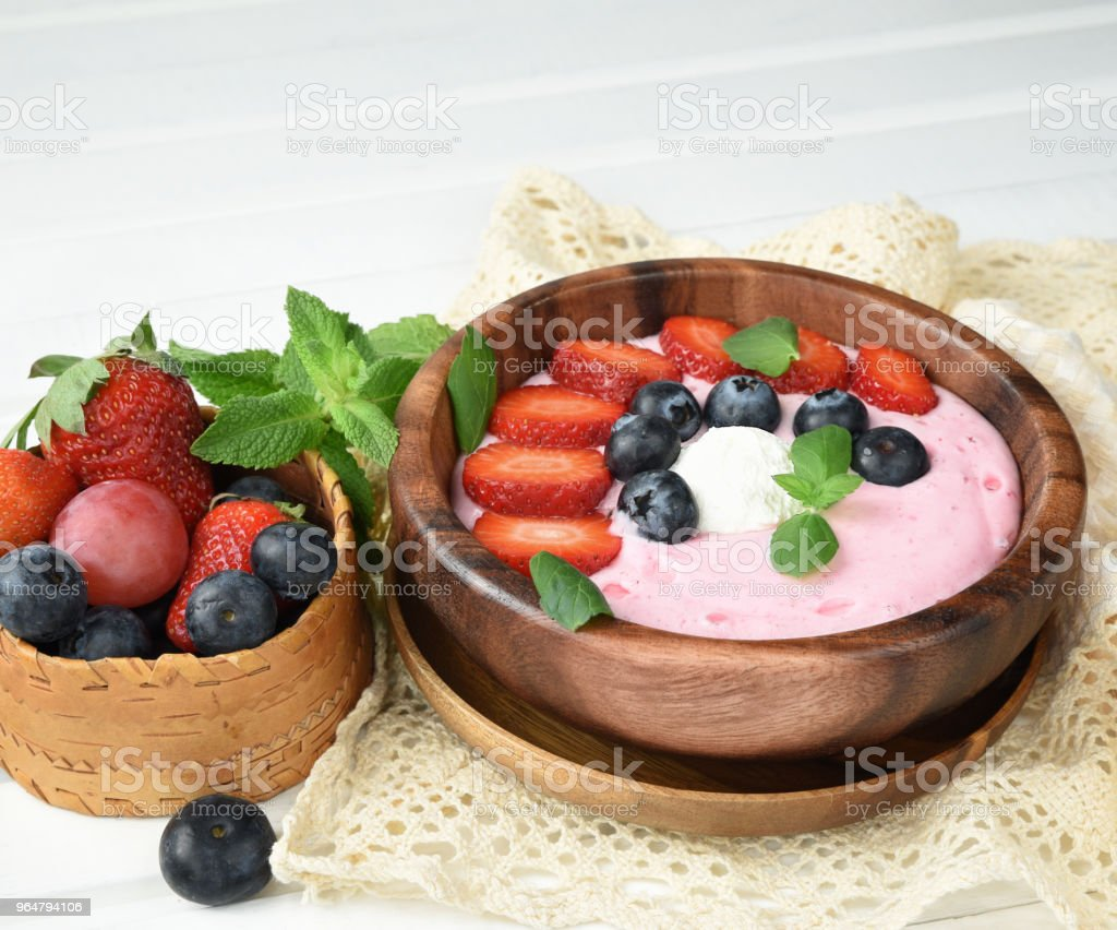 Ideas for healthy summer breakfast op dessert. Smoothies in bowls with strawberry, blueberry berry. With oatmeal, fresh berries. White wooden table. Copy space royalty-free stock photo