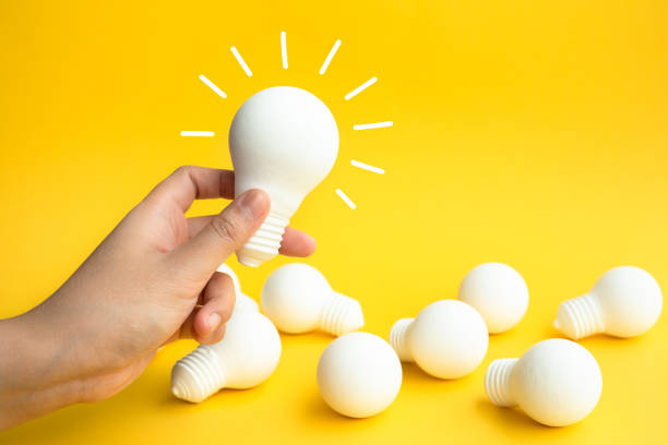 Ideas inspiration concepts with female hand holding lightbulb on pastel color background stock photo