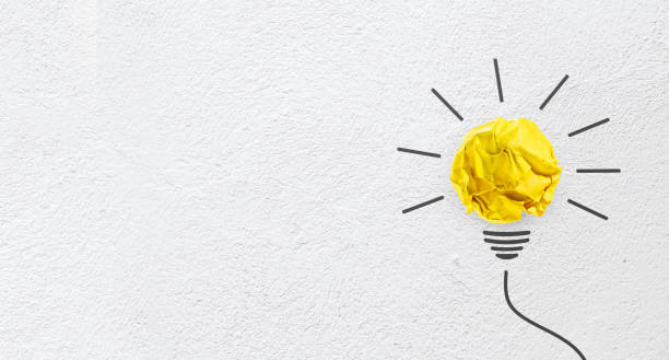 ideas with yellow paper crumpled ball on wall( lightbulb ). - single word stock photos and pictures