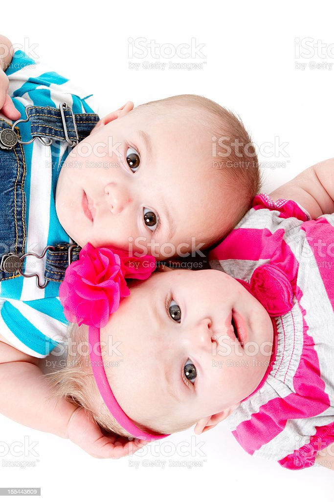 Identical twin babies lying in opposite directions stock photo