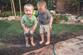 A stock photo of Identical twin brothers playing with a mud in the backyard. Photographed using the Canon EOS 1DX Mark II