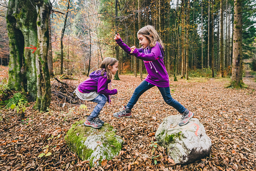 Identical twins are jumping from rocks in forest on hiking.