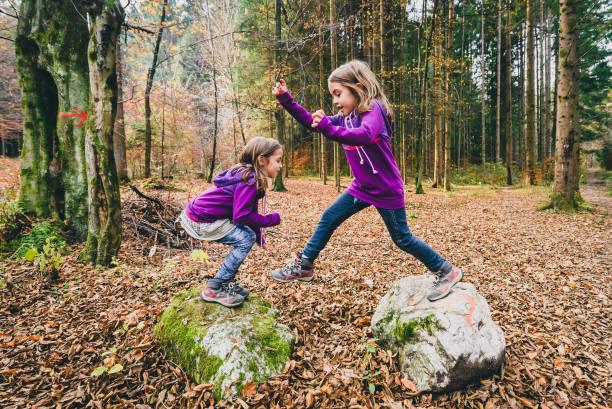 identieke tweelingen springen uit de rotsen in het bos op wandelen. - bos spelen stockfoto's en -beelden