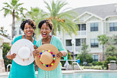 Two mature African-American women in their 40s, identical twins, standing on a pool deck side by side, laughing. They are holding wide-brimmed sun hats.