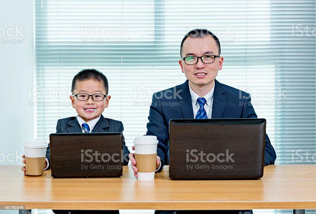 Padre e hijo usando computadoras portátiles - foto de stock