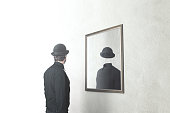 identity absence surreal concept; man in front of mirror reflecting himself without face