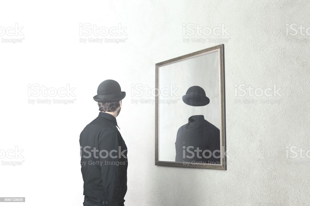 identity absence surreal concept; man in front of mirror reflecting himself without face stock photo