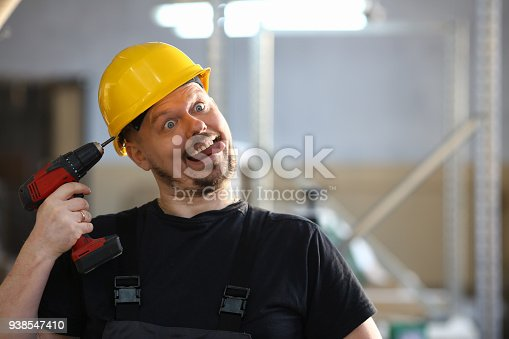 Idiot worker using electric drill portrait. Manual job DIY inspiration improvement fix shop yellow helmet joinery startup idea industrial education profession career concept