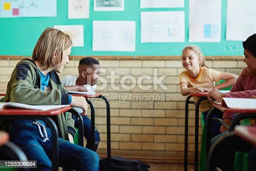 Shot of a group of children talking in a classroom