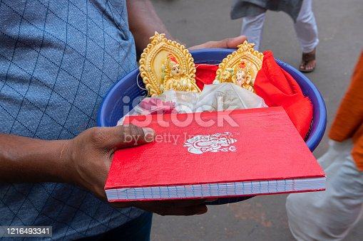 Young man carrying colourful clay idols of Goddess Laxmi, Lord Ganesh and new accounts notebook with Ganesha symbol on it for worship, in a plastic bucket. Image shot at Kalighat, Bengali New year,