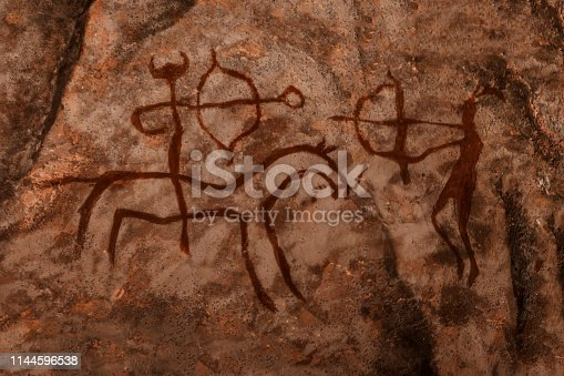 iDrawing of ancient hunters on the wall of the cave. history of antiquities, archaeology.